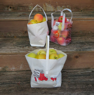 Bags of apples, from different orchards, sitting on wooden steps