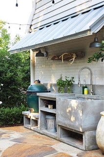 An outdoor kitchen made of concrete with a green barbecue grill.