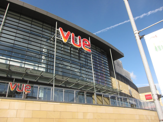 Looking up at the Vue Cinema in Halifax - lots of glass - with a blue sky and plane entrail