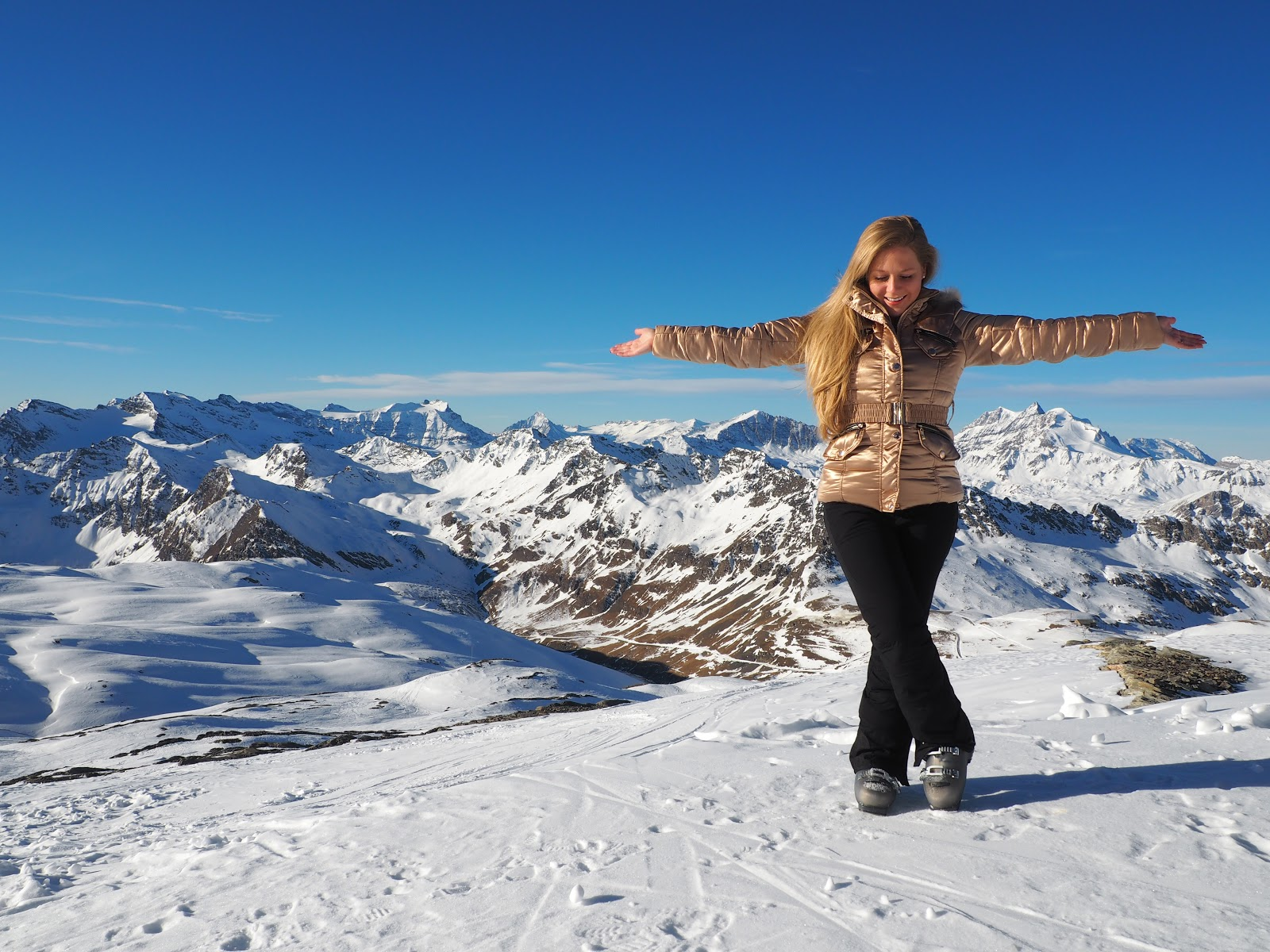 Girl wearing gold jacket standing on top of a snowy mountain in Val d'isere, France
