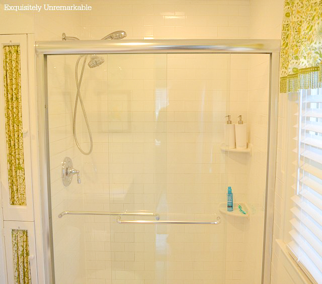 Glass shower doors in a white bathroom with green accents