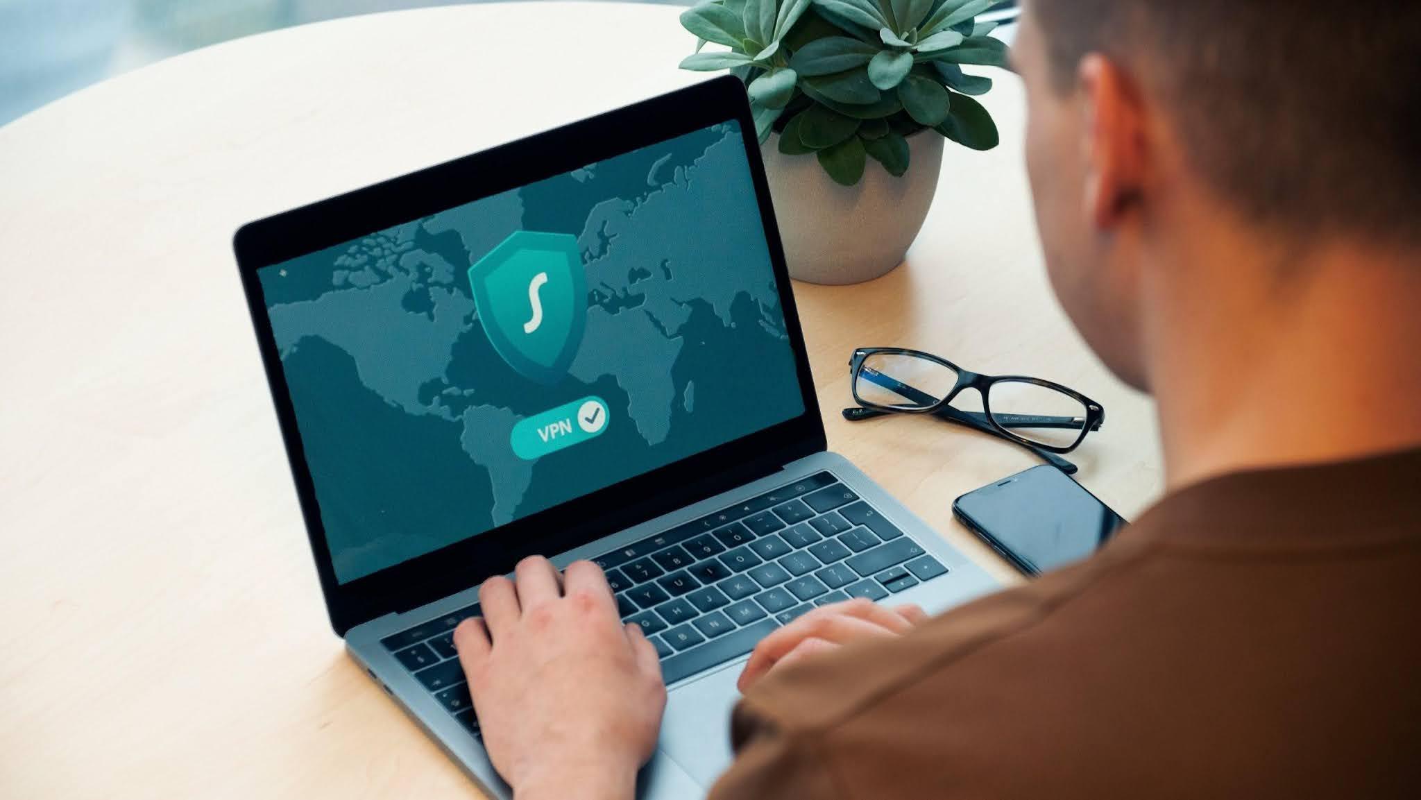 Homem acessando a internet em notebook através de uma VPN