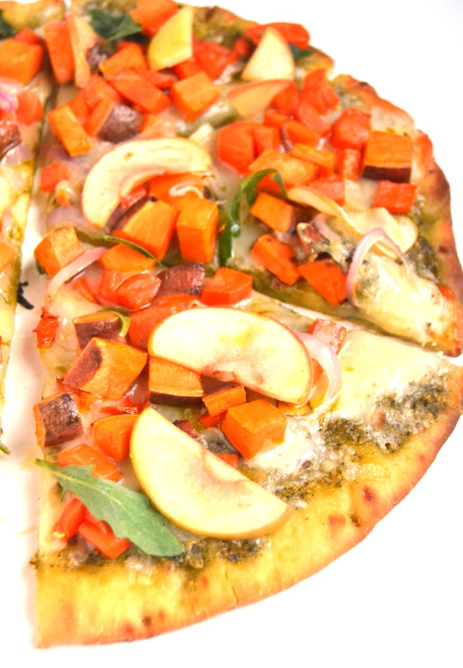 White Cheddar and Pesto Roasted Vegetable Pizza is a flavor loaded, easy pizza with roasted sweet potatoes, carrots, apples and red onions and is topped with fresh arugula for a peppery bite. www.nutritionistreviews.com