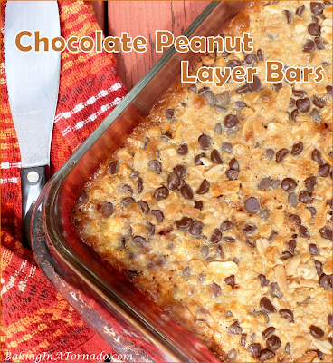 Chocolate Peanut Layer Bars start with chocolate graham cracker crust and are layered with candy bits, dark chocolate chips, peanuts and more. Simple to make, addicting to eat. | Recipe developed by www.BakingInATornad.com | #recipe #bake