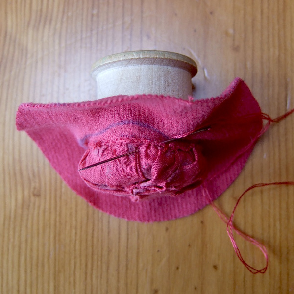 Pushing the spool through the red fabric circle and stitching in place