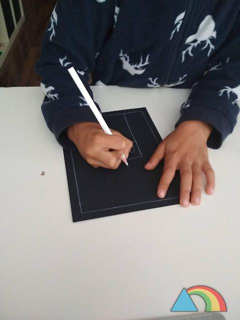Niño haciendo dibujos otoñales con una cera blanca sobre cartulina negra