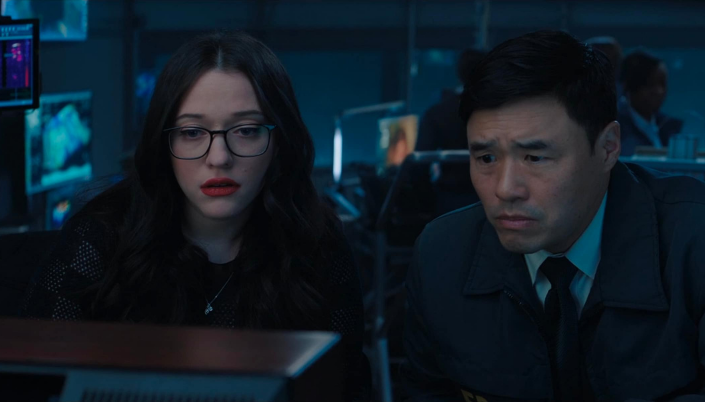 Imagem: a personagem Darcy, uma jovem branca com cabelos castanhos longos, usando um casaco, ao lado do agente Woo, um homem asiático em um uniforme do FBI, com gravata por baixo assistindo a tela de uma televisão antiga, por trás diversos monitores e agentes da S.W.O.R.D. por trás.