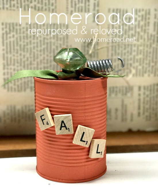 aluminum can pumpkin with scrabble letters and glass knob with newspaper background