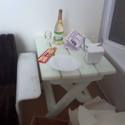Sofa and sidetable. On the table is a bottle of wine and a wine glass, a takeout menu, chopsticks, empty plate and cardboard takeaway container. In front of the table is an empty packing box and pile of discarded packing paper.