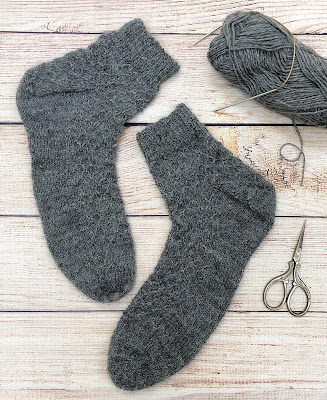 Grey socks knitted with DROPS Fabel and slipped stitches, heel flaps, wedged toes, and Jeny's stretchy slipknot cast-on
