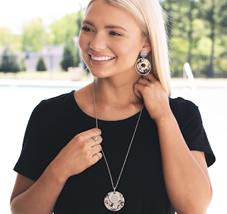 girl wearing matching monogrammed earrings and necklace