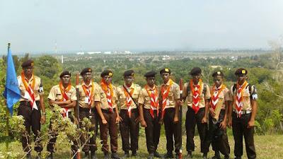 Tampak para pemuda berfoto bersama dengan latar belakang kilang minyak PT. Arun