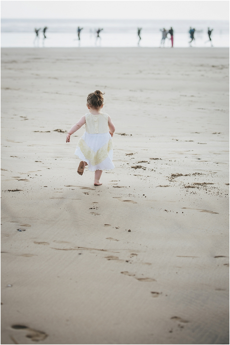 A toddler running along the beach at Saunton Sands
