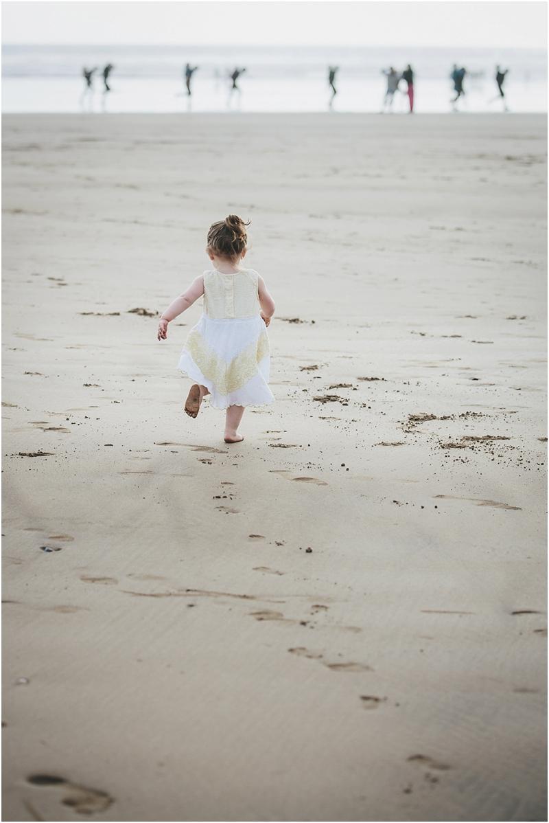A toddler running along the beach at Saunton Sands
