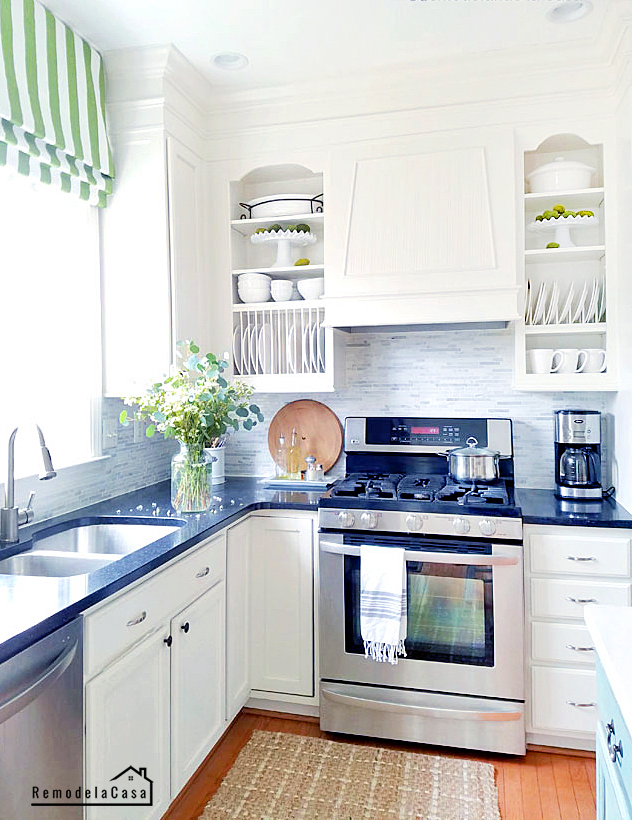 White kitchen with green Roman shade and decor accents