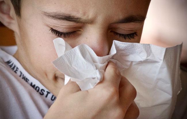 Bambino che si soffia il naso per il raffreddore
