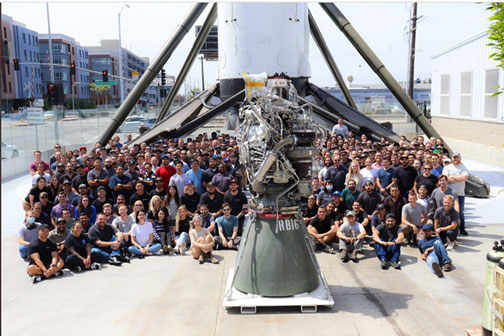 100th Raptor engine produced by SpaceX, with Falcon 9 in the background (Source: SpaceX)