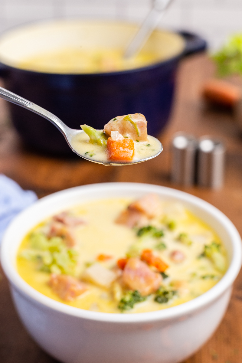 Closeup sideview of a white bowl full of Keto Cheesy Ham Chowder with a spoonful of it closer to the camera and a blue pot full blurred in the background.