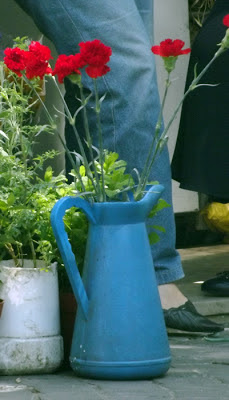 vaso azul com  cravos vermalhos