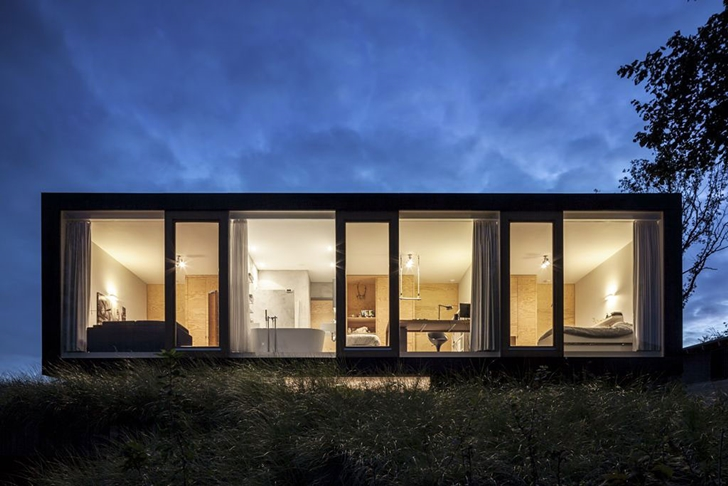 Street face of Modern Villa V by Paul de Ruiter Architects at night