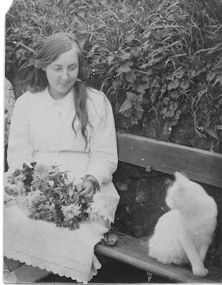 Seated girl with flowers and white cat