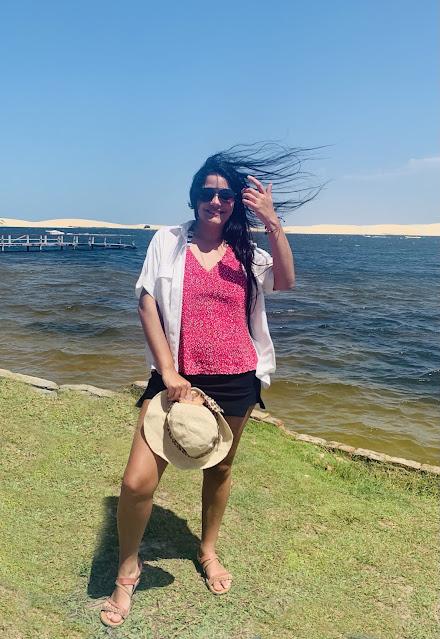 mulher morena, jovem, cabelo preto, oculos escuros, blusa rosa e blaser branco em uma lagoa azul e verde