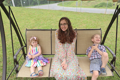 a smiling woman in a flower covered long dress sits on a swing with two small children