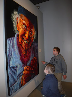 blonde boys in a navy blue sweater and a gray sweatshirt are seen from the side admiring a painting of an old woman at the Sioux City Art Center