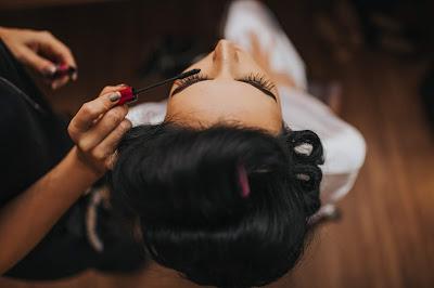 Maquilladora aplicando rímel a una novia