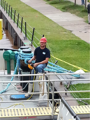 A crew member works the control of the crane