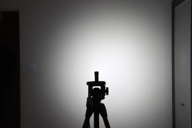 Wiązka światła z Olight H1 Nova. Latarka w odległości ok. 1,5m od ściany.