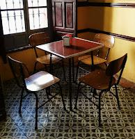 Mesa dw café con cuatro sillas.