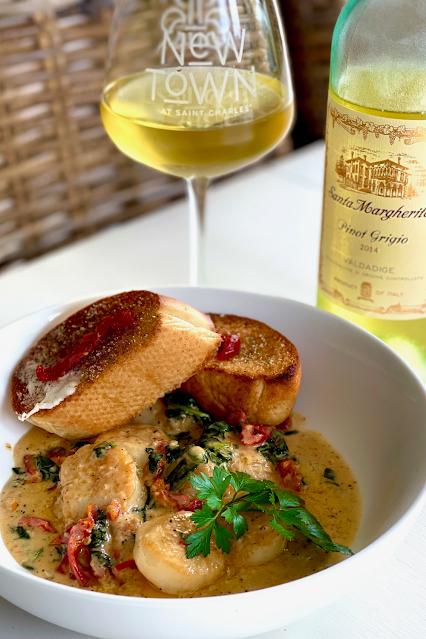 A creamy scallop dish with a glass of pinot grigio wine