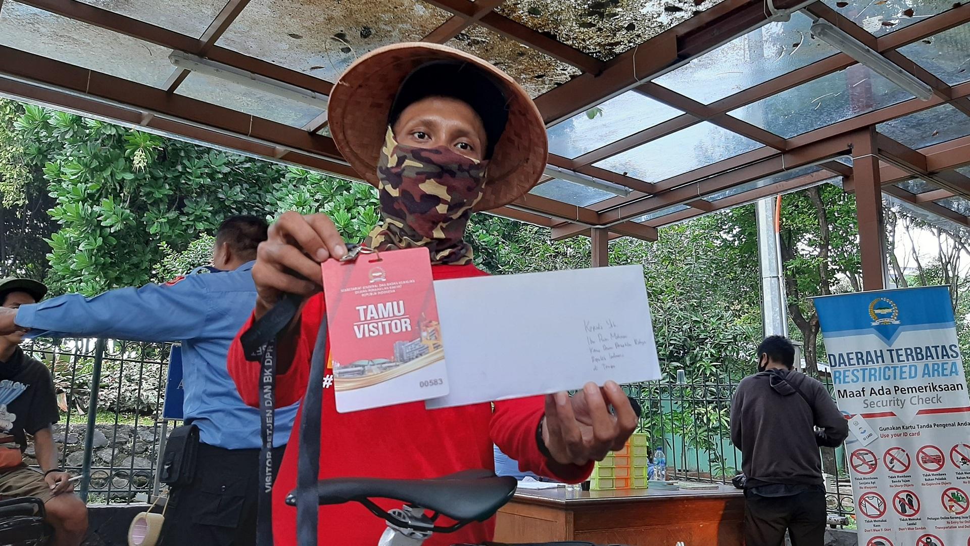 Jarpo menunjukkan kartu identitas pengunjung bersama surat untuk Ketua DPR