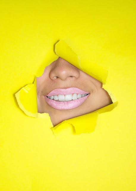 Girl smiling through yellow paper sheet; Photo by Hana Lopez on Unsplash