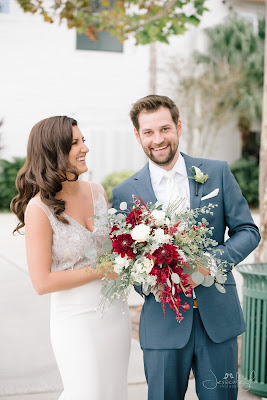 laughing bride and groom with red bouquet