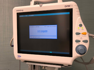 The screen of an IV pump displaying a white box with big blue letters: STANDBY