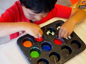 kid art- boy mixing glue sun catcher paint