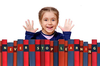 "girl with excited expression holding hands up over line of books with words ""Never Stop Learning"" on the spines"