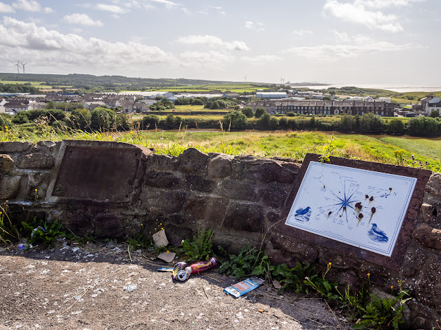 Photo of broken glass and other litter in one of the viewing areas on Mote Hill, Maryport. The information board has also been vandalised