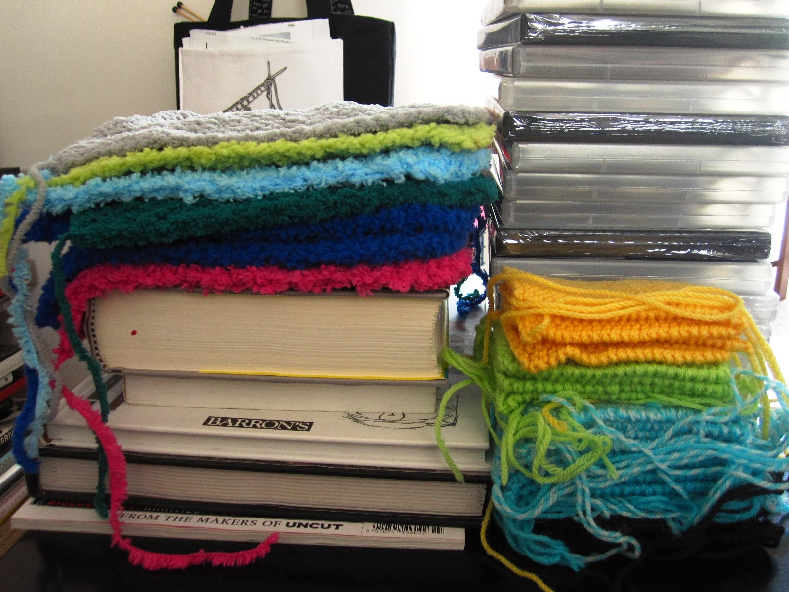 Piles of books, DVDs and rainbow-coloured stacks of knitted rectangles with trailing yarn ends