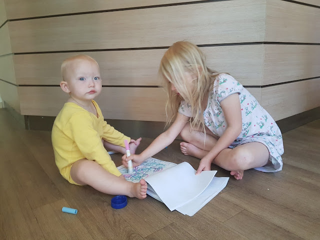 A toddler sitting on wooden floor next to her big sister while big sister colours in her colouring book