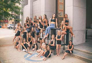 young dancers in various black dance costumes lean against a downtown building and smile