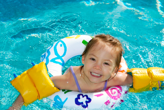 Image of a happy child in the pool wearing water wings and a float ring that you may use in you swimming Lesson ideas