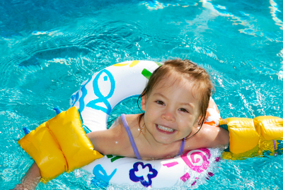 Picture of a happy  little girl in the pool wearing floaties and float ring. Confidence, when you learn how to swim, is always very important in new swimmers.