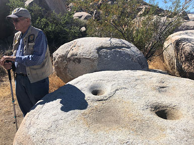 Volunteer State Parks docent, Sam Webb, explains prehistoric mortars on our two hour hike (Source: Palmia Observatory)