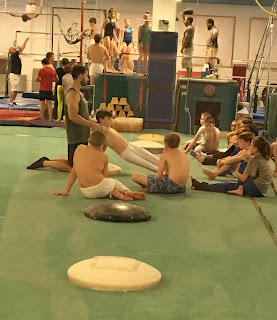 Group of teen boys sitting on a gymnastics mat learning from coach