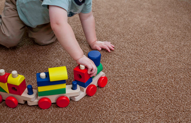 Child plays with a train on his carpeted bedroom floor