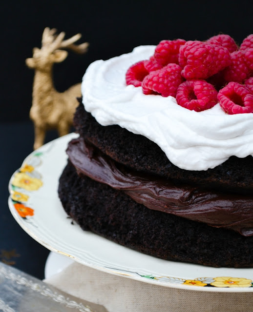 Vegan chocolate cake with whipped coconut cream, topped with raspberries