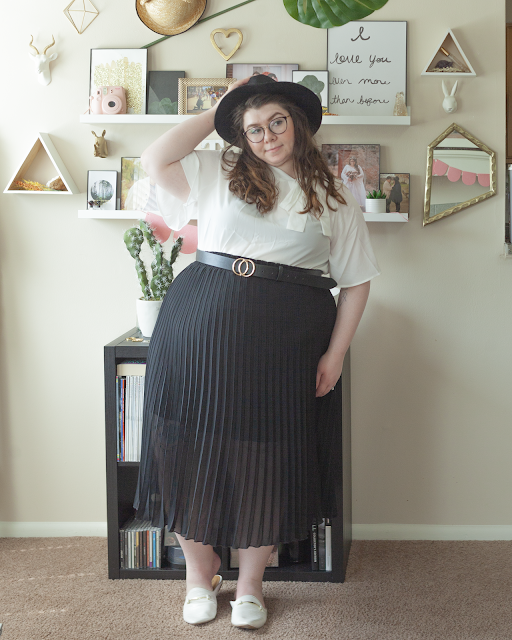 An outfit consisting of a white blouse with flouce sleeves and tie up neck, tied in a bow on the right side, tucked into a black pleated midi skirt and white mules.